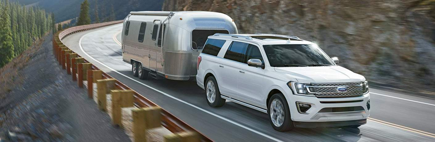 2018 Ford Expedition white front towing trailer on road