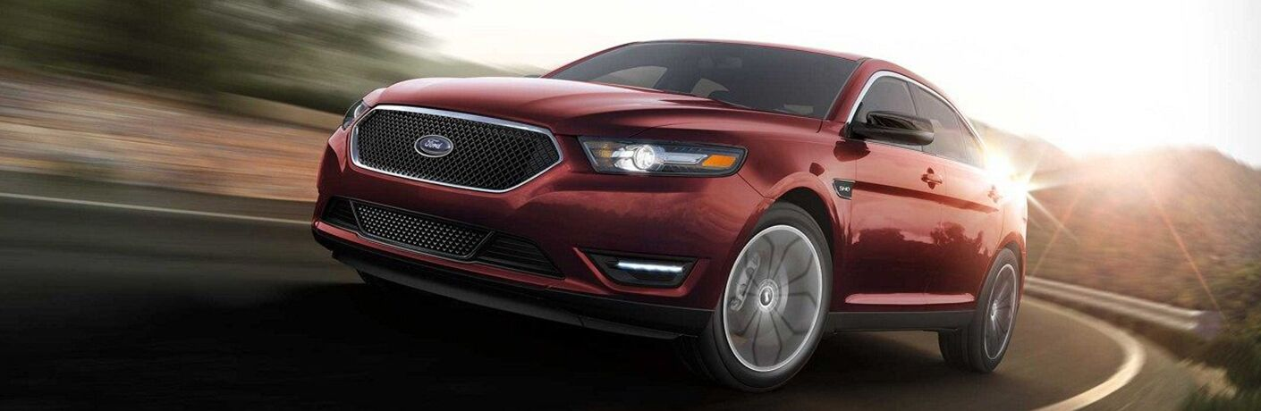 Red 2019 Ford Taurus driving down road
