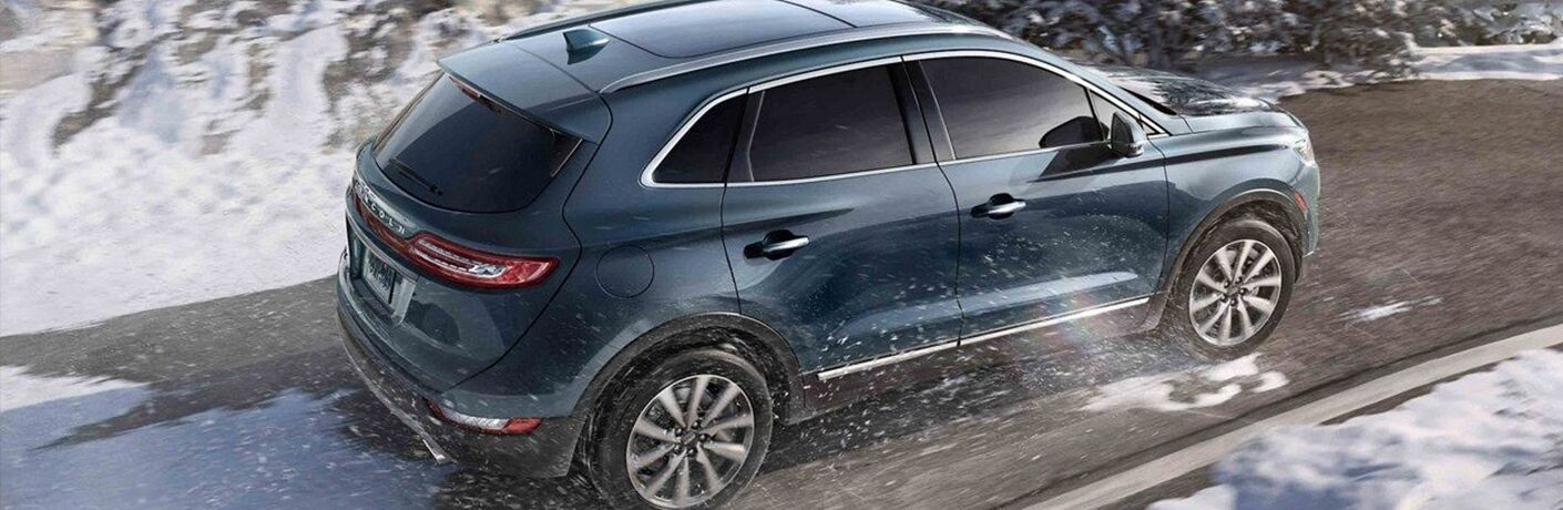 Navy blue 2019 Lincoln MKC driving down snowy road