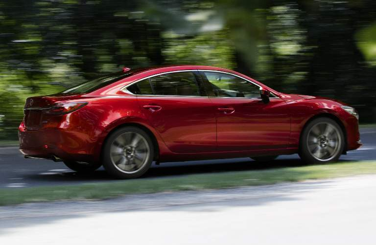 Red 2019 Mazda6 driving by a forest