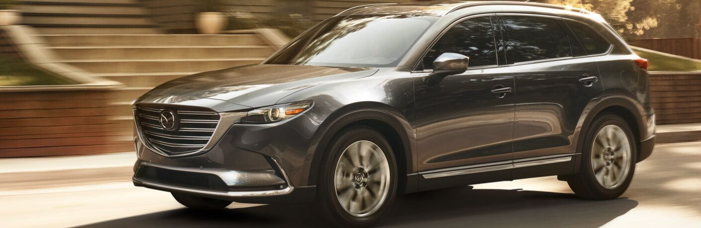 Dark Grey 2019 Mazda CX-9 Driving by a House