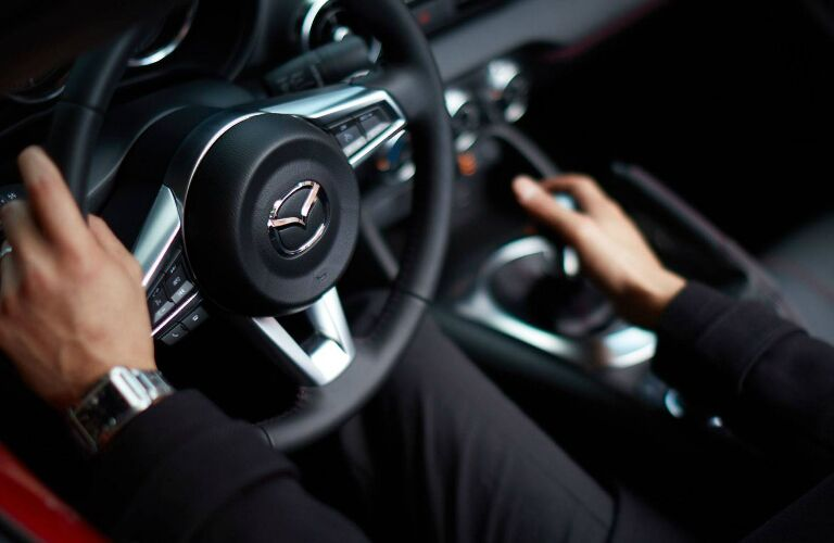 The Left Hand on the Steering Wheel and the Right Hand on the Shift Knob of the 2019 Mazda MX-5 Miata RF