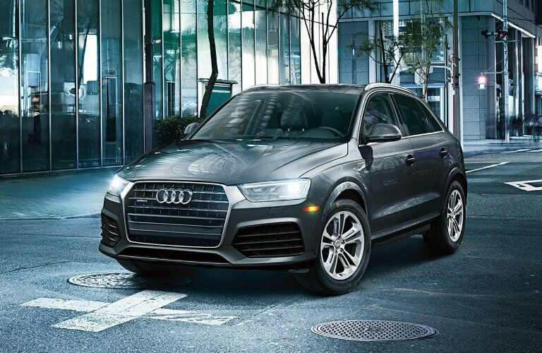 gray Audi Q3 parked by window-lined building
