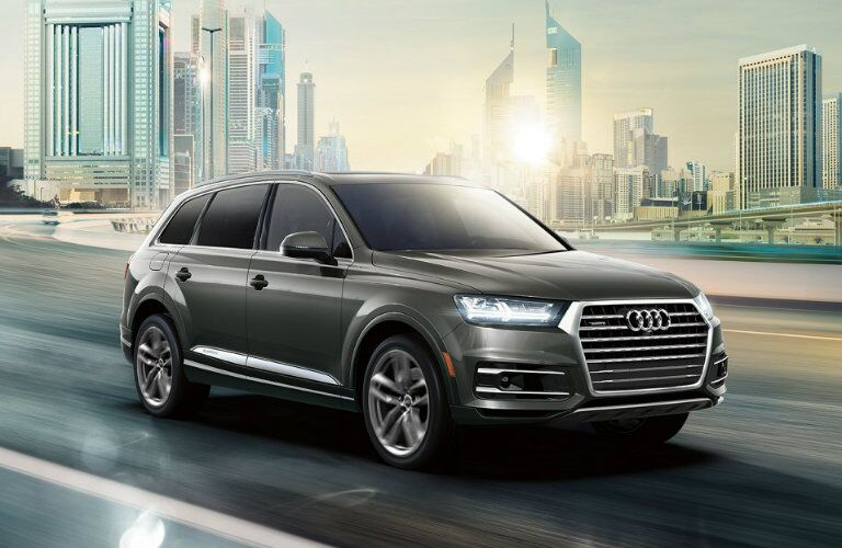 gray Audi Q7 driving down city highway