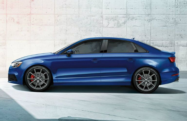 side profile of blue Audi S3 in front of concrete wall