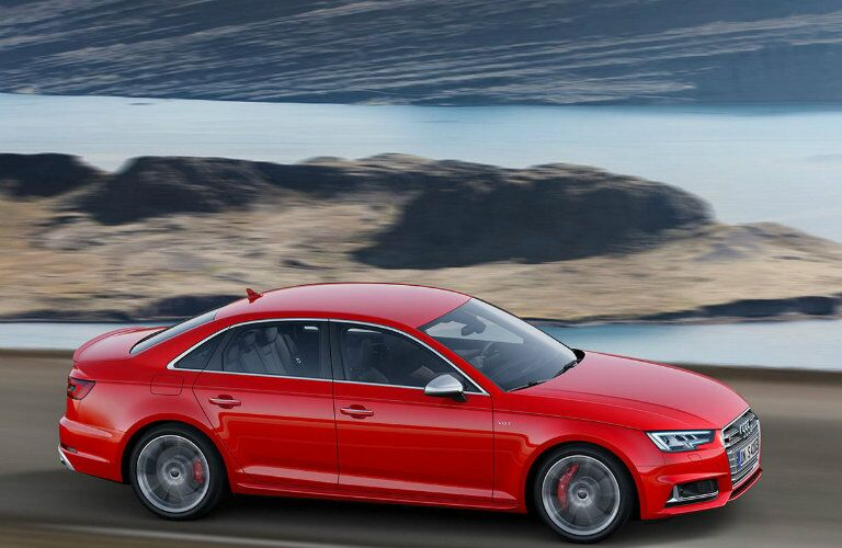 red Audi S4 driving along water-side highway