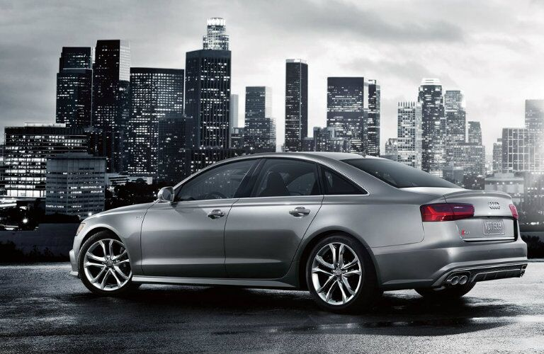 gray Audi S6 with city skyline in background