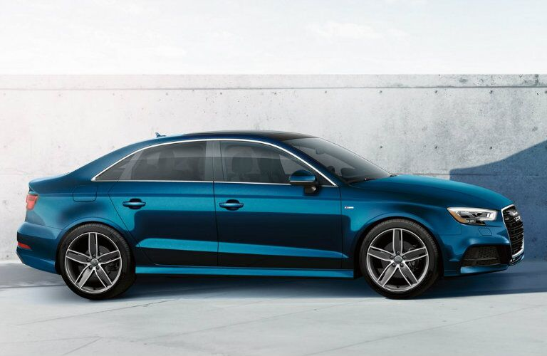 side profile of blue Audi A3 parked by concrete wall