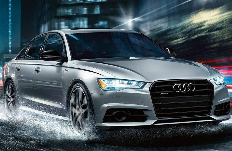 2018 audi a6 in silver driving through rain at night in philadelphia pennsylvania