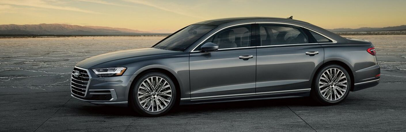 2019 Audi A8 exterior side shot with gray color paint job parked on a cracked plateau of earth and cement as the sun sets in the background