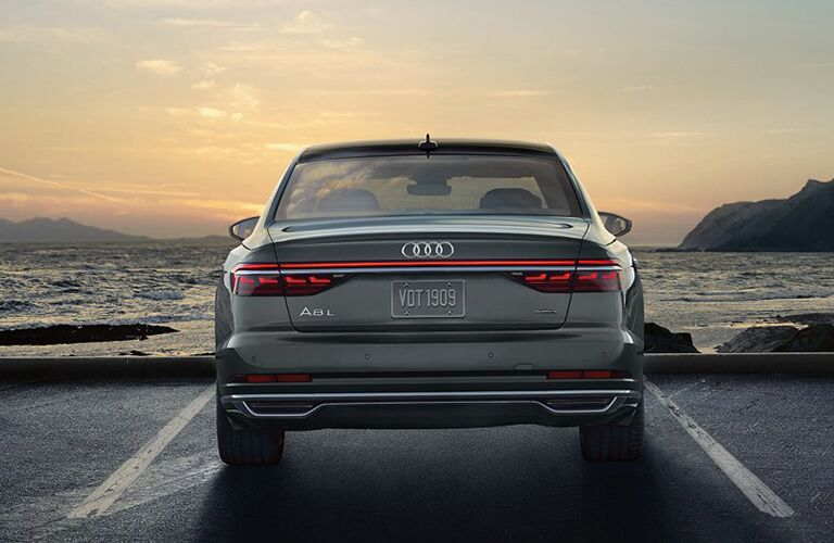 2019 Audi A8 exterior rear shot parked in a parking lot with the sea and ocean waves in front of it