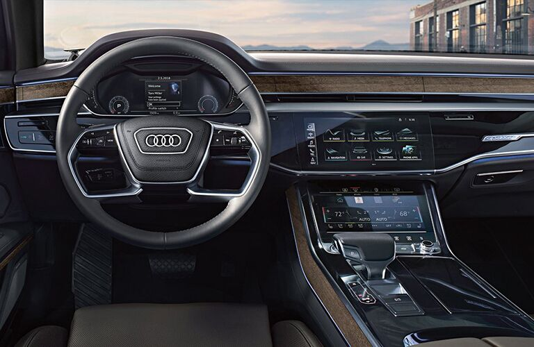 2019 Audi A8 interior shot of driver's seat view of steering wheel with audi badge and dashboard screens and infotainment