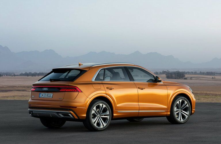 side profile of orange Audi Q8 parked in front of hazy mountain
