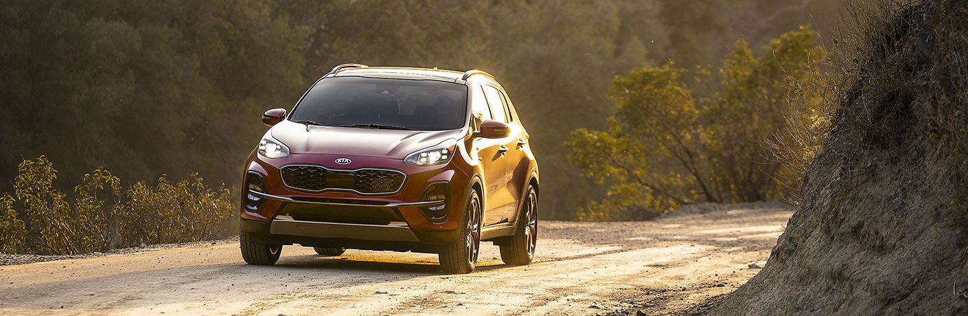 Red 2020 Kia Sportage driving on a rural road