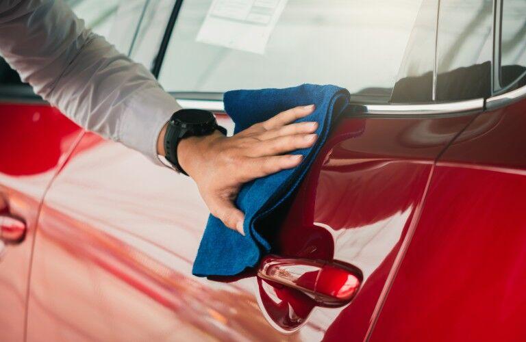 Dealership employee wiping down a car