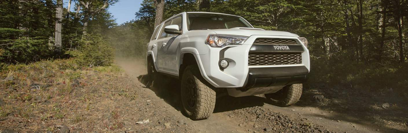 2018 Toyota 4Runner driving through tree-lined back road