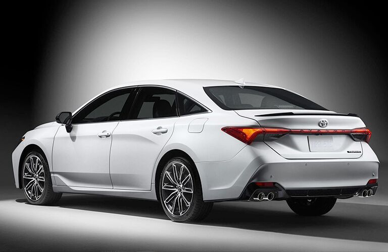 Exterior view of the rear of a white 2019 Toyota Avalon parked in a white room