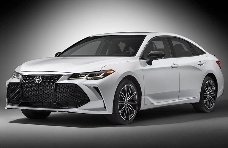 Exterior view of the front of a white 2019 Toyota Avalon parked in a white room