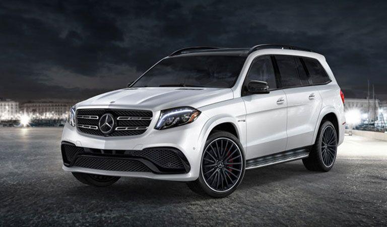 white 2018 Mercedes-Benz GLS parked in a vast courtyard at night