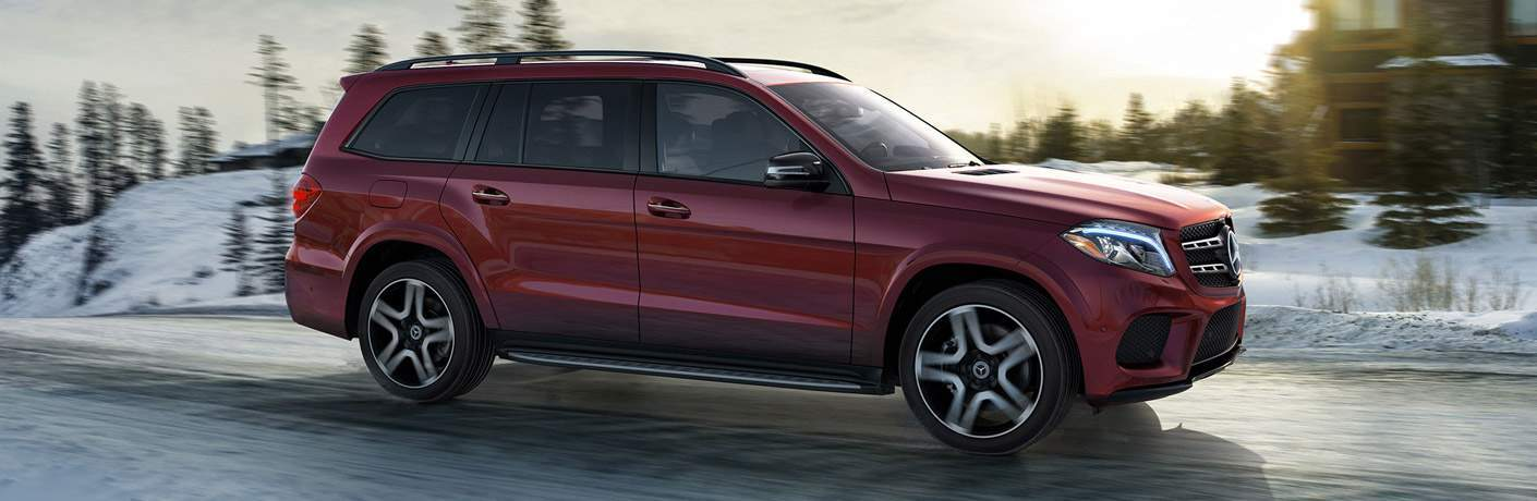 side profile of maroon 2018 Mercedes-Benz GLS driving in winter