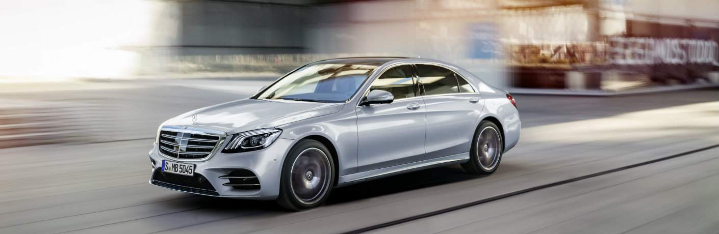 silver 2018 Mercedes-Benz S-Class driving past building