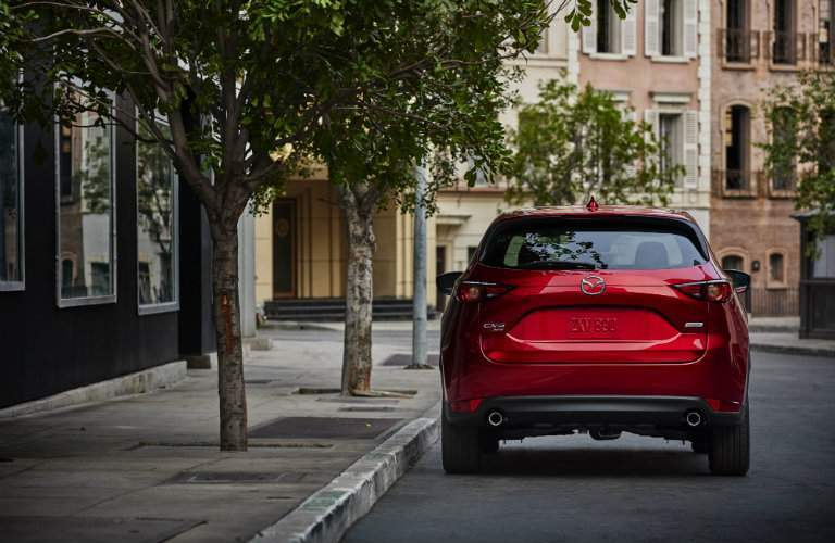 rear of red mazda cx5 parked on side of road