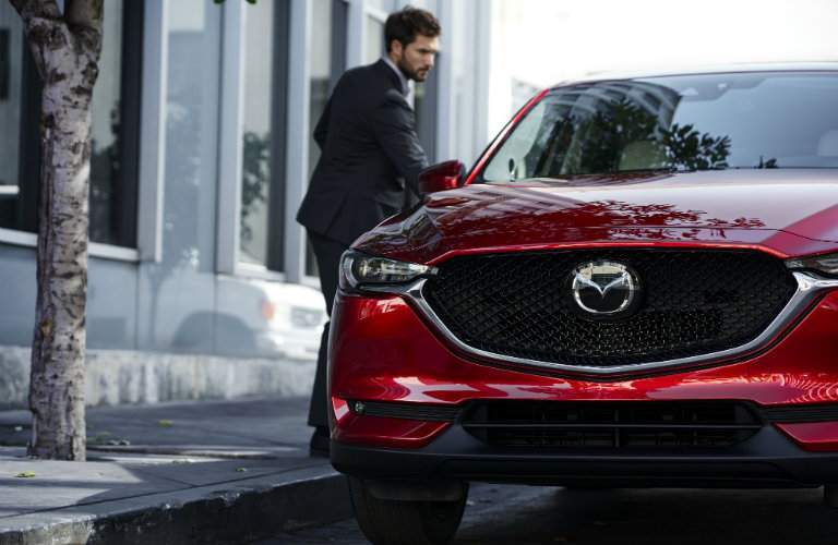 man getting into red mazda cx5