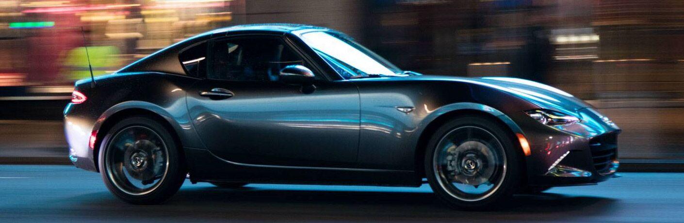 silver mazda mx-5 miata driving at night in city