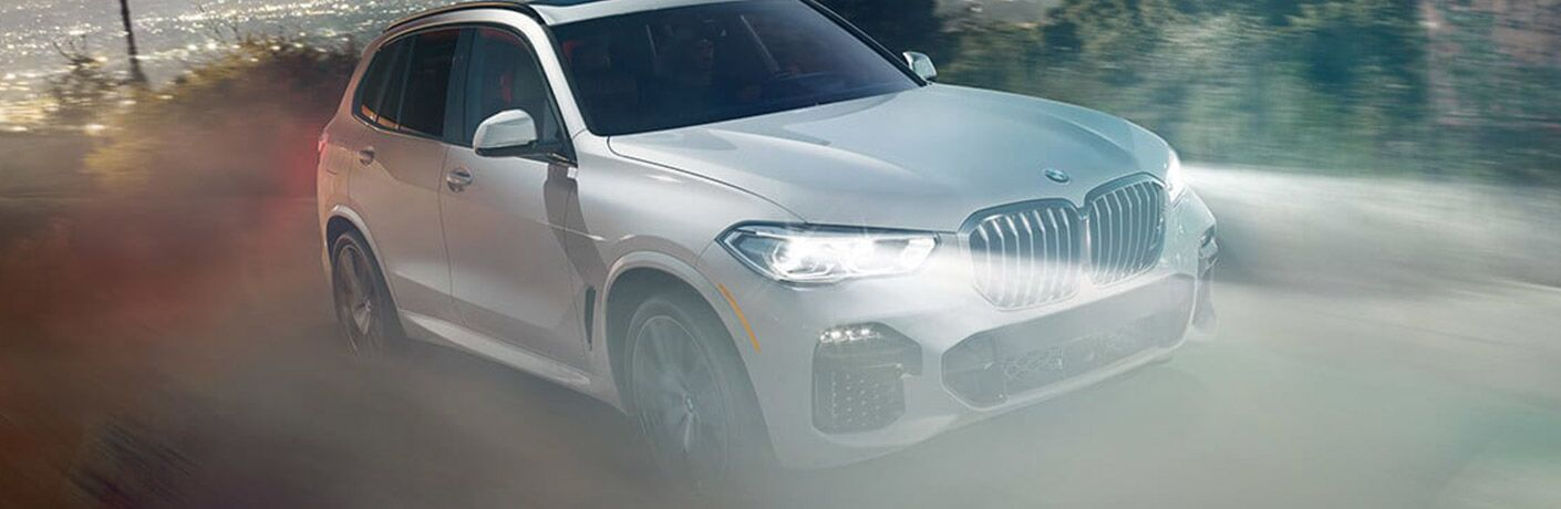 silver 2019 BMW X5 in fog with bright head lights