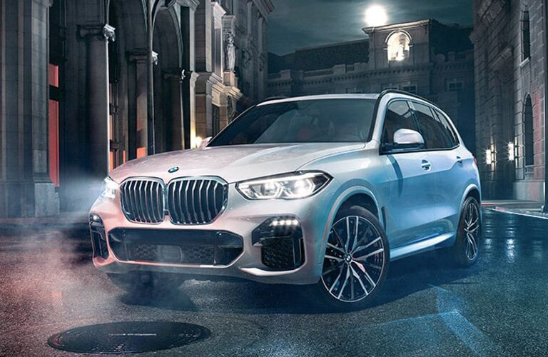 silver 2019 BMW X5 in rainy city front side view