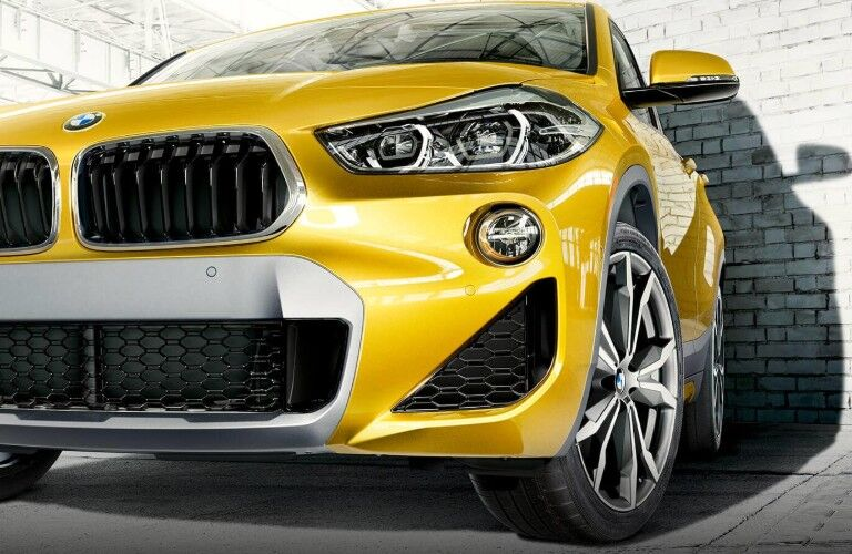 Yellow 2019 BMW X2 on brick wall background