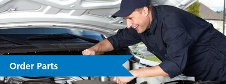 Young Mechanic Smiling Under the Hood of a Car with Blue Banner and White Order Parts Text