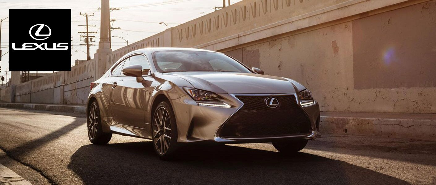 2015 Lexus sedan driving down an empty highway on a sunny day