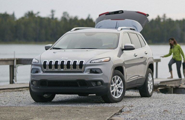 2016 Jeep Cherokee in grey parked near a lake with the rear hatchback open