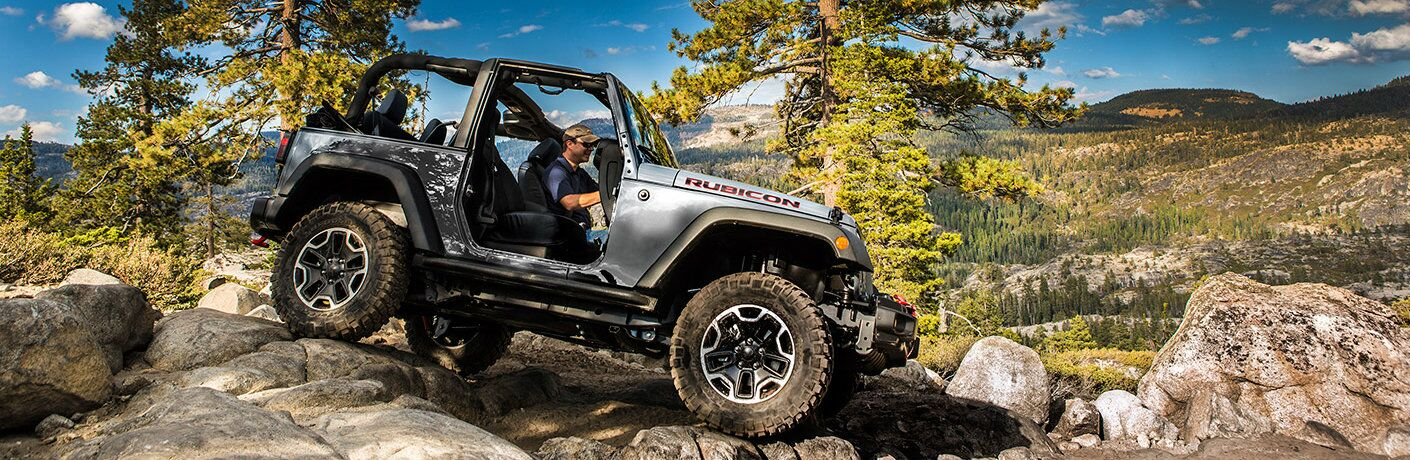 2017 Jeep Wrangler descending a rocky hill in the mountains