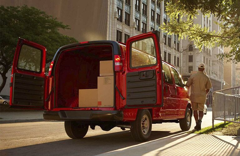 2017 Chevy Express cargo van parked on the side of the road with the rear doors open_o