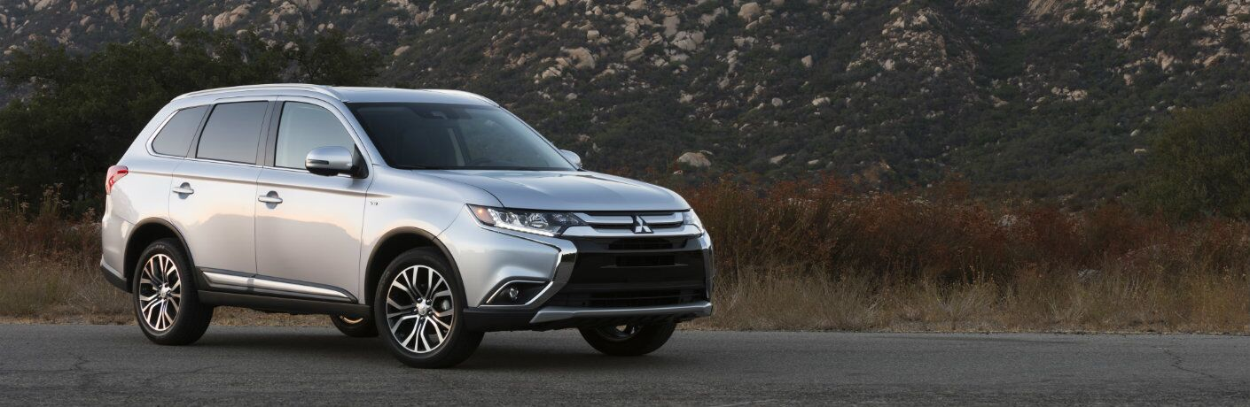 2017 Mitsubishi Outlander parked on pavement at the base of a mountain