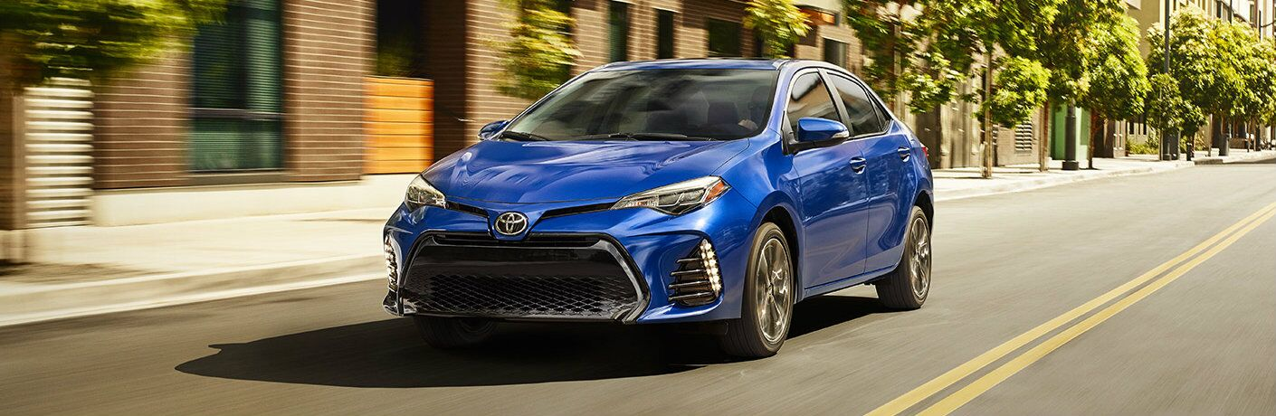 2017 Toyota Corolla model in blue driving down an empty city street
