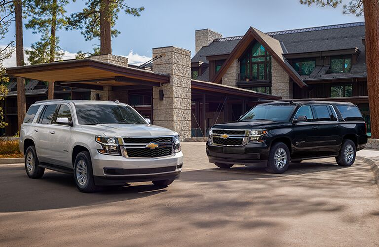 Two 2019 Chevrolet Tahoe models outside of large home