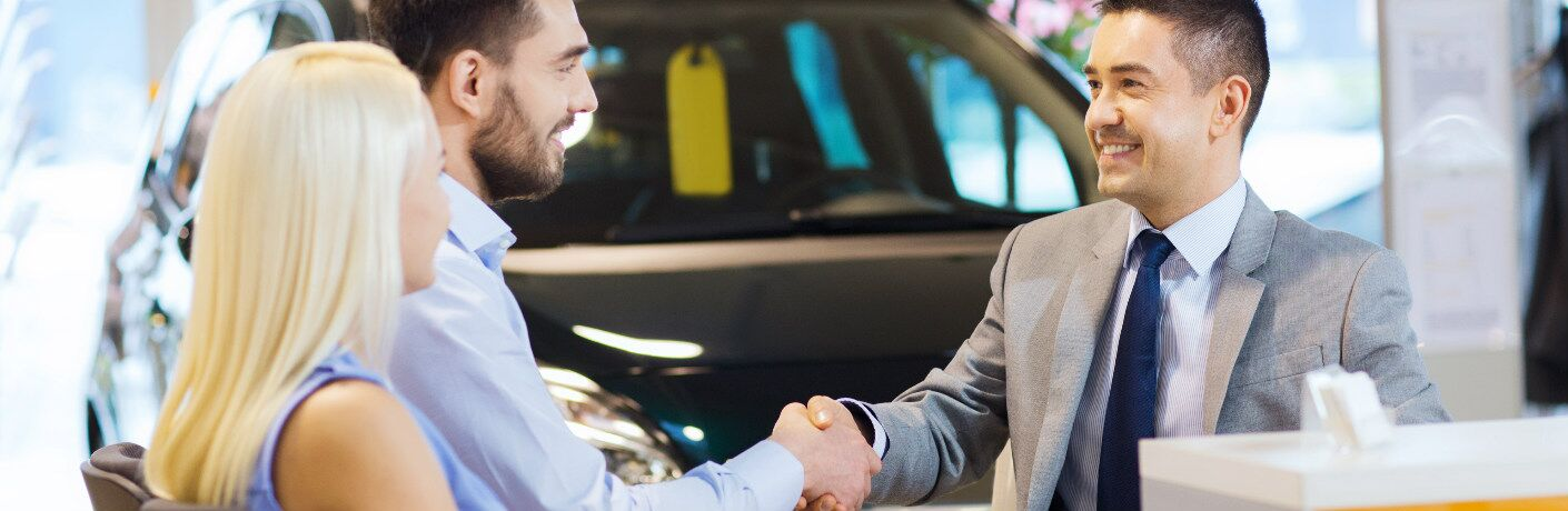 A couple shaking hands with an employee at a car dealership