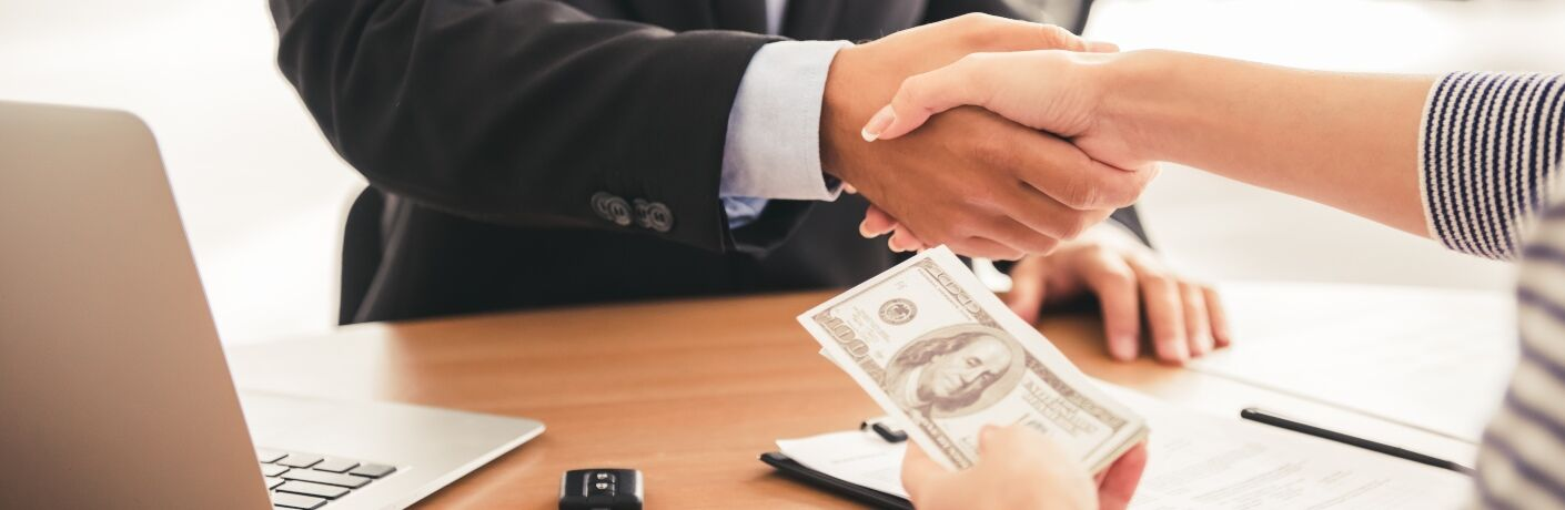 Two people shaking hands with money