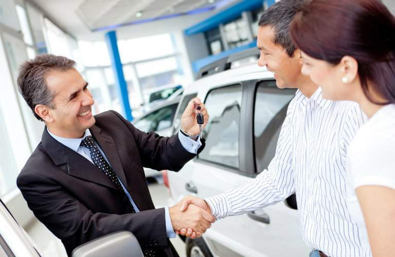 Salesman handing a car key to a man and woman