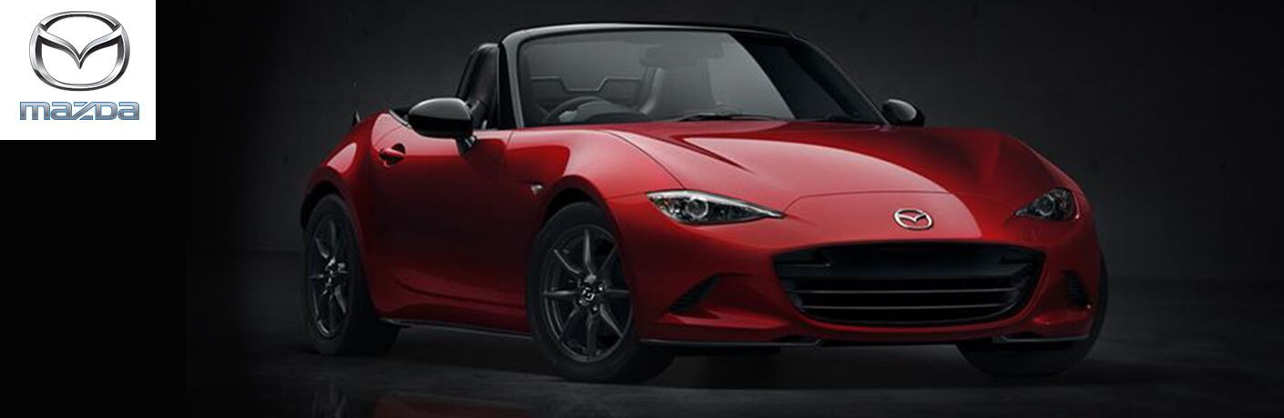 Red Mazda MX-5 Miata on Dark Background with White, Silver and Blue Mazda Logo in Upper Left Corner