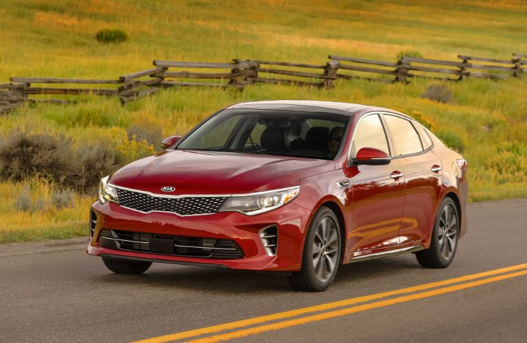 2018 Kia Optima exterior front shot red pain parked in the wilderness by a field of grass and a farm fence