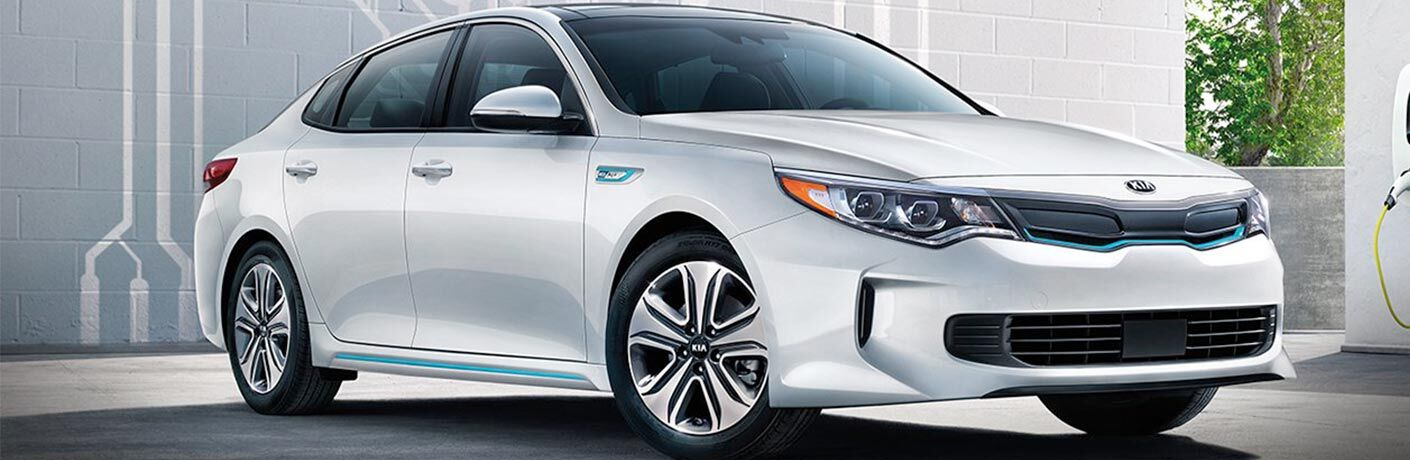 2018 Kia Optima Plug-In Hybrid exterior shot parked in the sunlight next to white walls and green tress in the background