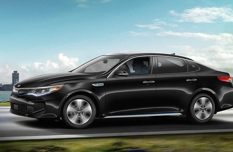 2018 Kia Optima Plug-In Hybrid exterior shot driving down road by grass and next to the sea river and cityscape background with cloudy blue sky