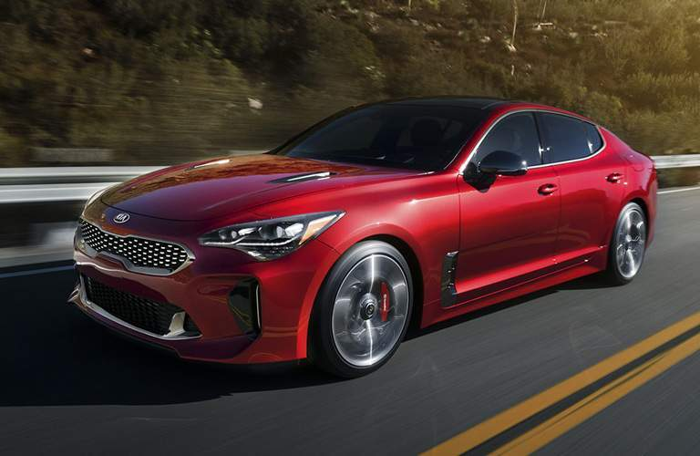 2018 Kia Stinger driving down highway with grassy hills