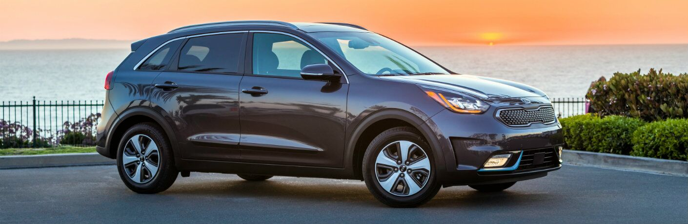 2018 Kia Niro Plug-In Hybrid exterior side shot gray paint job parked at a clearing near the sea at sunset