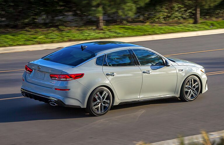 2019 Kia Optima exterior overhead side shot driving on a forest highway towards the sunset