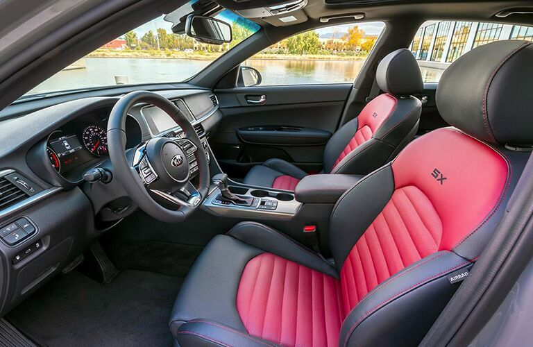 2019 Kia Optima interior side shot of front seating upholstery and design along with steering wheel and dashboard